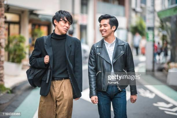 東京を歩いて話すカジュアルな若い日本人男性 - レザージャケット ストックフォトと画像