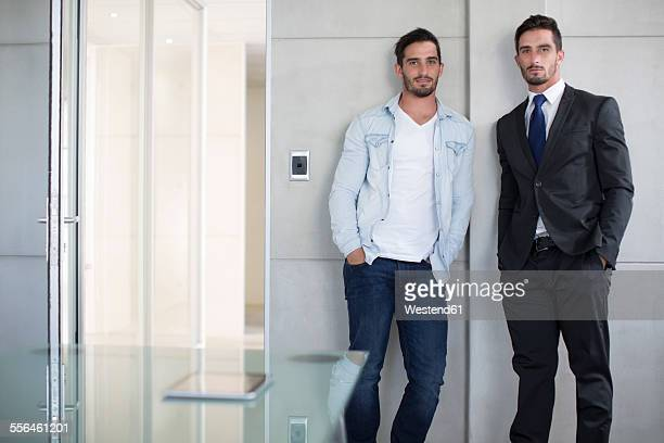 casually and formally dressed twin males in office - twin stock pictures, royalty-free photos & images