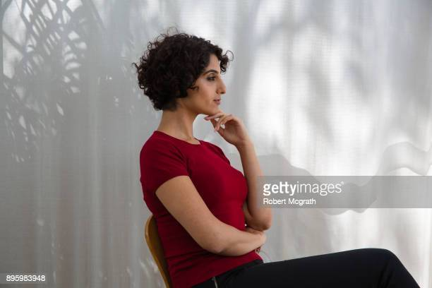 Casually dress professional woman sits in front of a shadowed curtain, listening and contemplating