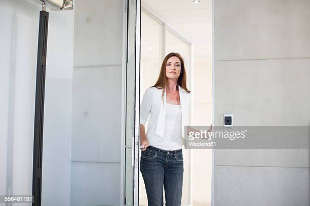 Casually dressed businesswoman opening boardroom door