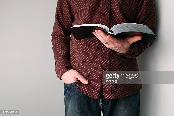 Casually Dressed Christian Guy Holding an Open Bible
