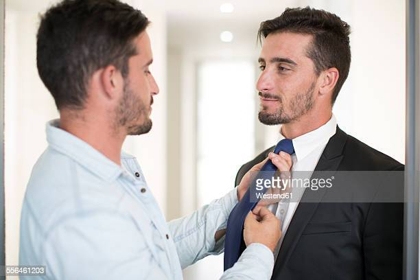 Casually dressed man adjusting tie of twin brother in office