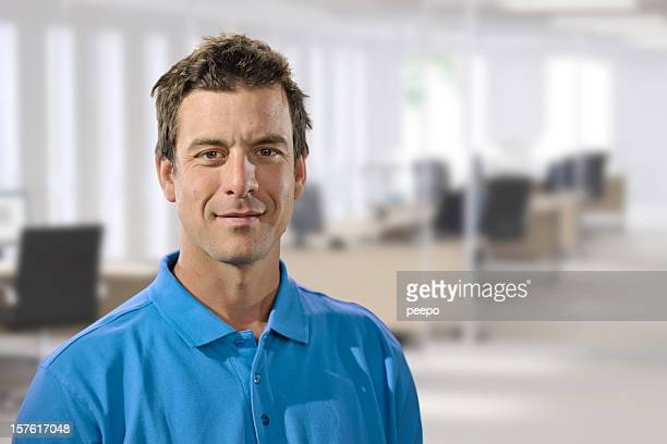 casually dressed man in office - polo shirt stock pictures, royalty-free photos & images