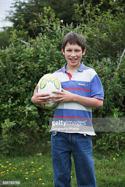 casually dressed young boy holding a rugby ball