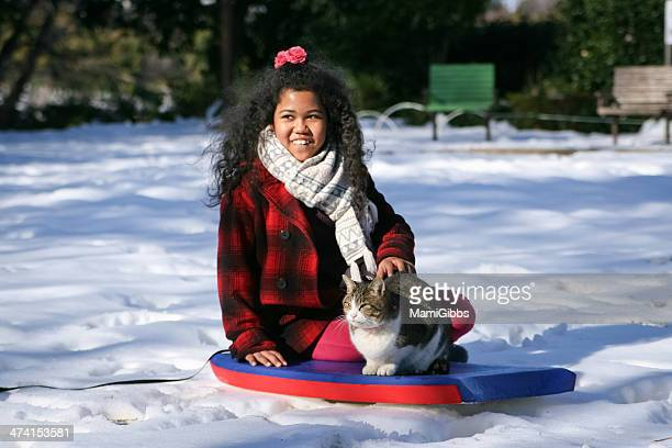 Cat and girl are sitting on top of the snow
