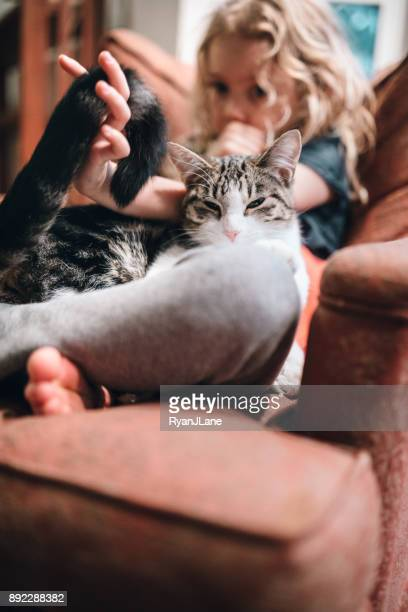 Cat Resting in Lap of Little Girl on Armchair