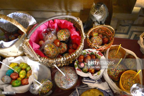 Cat sits before a table with cakes and colored eggs during an Orthodox Easter ceremony at the Pokrovsky Cathedral in Saint Petersburg on April 15 on...