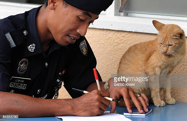 A cat watches as a police officer notes down the number of voters inside a polling station in the northeastern Terengganu state on January 17 2009...