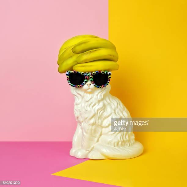 cat wearing sunglasses and banana wig/hat - sculptuur stockfoto's en -beelden