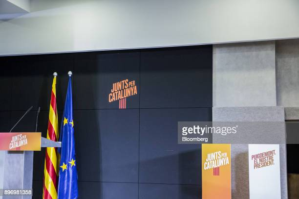 A Catalan and a European Union flag hang beside a speaker's podium at the headquarters of the Junts X Catalunya party in Barcelona Spain on Thursday...