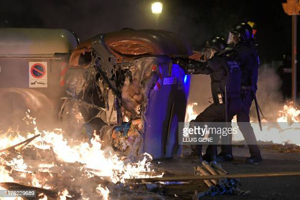 Catalan antiriot police officers pull a melted skip used as a barricade by protesters during a demonstration called by the local Republic Defence...