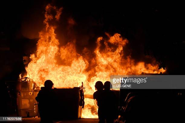 Catalan antiriot police officers stand close to a burning barricade during a demonstration called by the local Republic Defence Committees in...