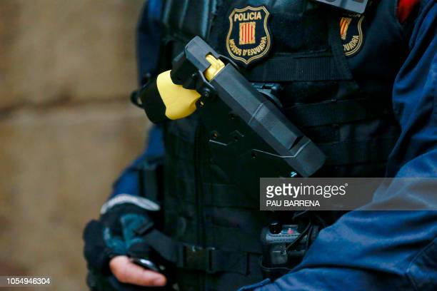 A Catalan autonomous police 'Mosso D'Esquadra' officer carries a 'Taser' electroshock weapon during a police operation against drug consuming and...