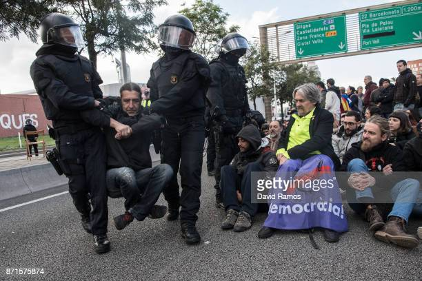 Catalan autonomous riot police officers remove demonstrators as they block a ring road during a regional strike on November 8 2017 in Barcelona Spain...