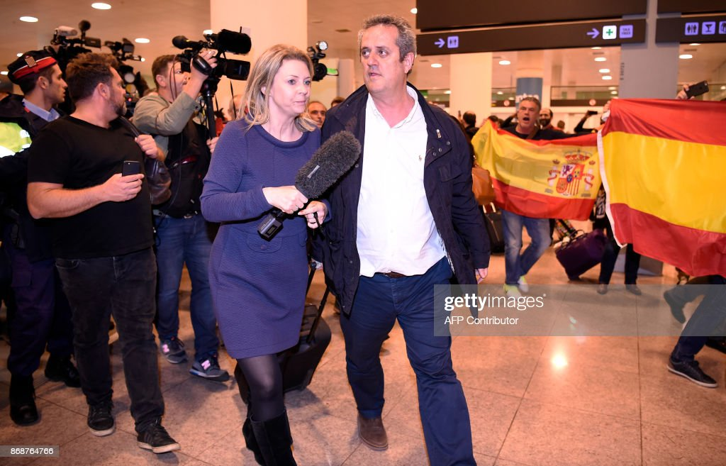 Catalan dismissed Interior chief Joaquim Forn (C) is followed by journalists as people with Spanish flags shout at him upon his arrival at El Prat airport in Barcelona after flying from Brussel on October 31, 2017. Spain's top criminal court today summoned Catalonia's axed separatist leader for questioning, hours after he appeared in Brussels insisting he remained the 'legitimate president' of a region now under direct rule from Madrid. The National Audience in Madrid, which deals with major criminal cases, summoned Carles Puigdemont and 13 other former members of his administration, dismissed by Spain's central government last week, for November 2 and 3. PHOTO / Josep LAGO