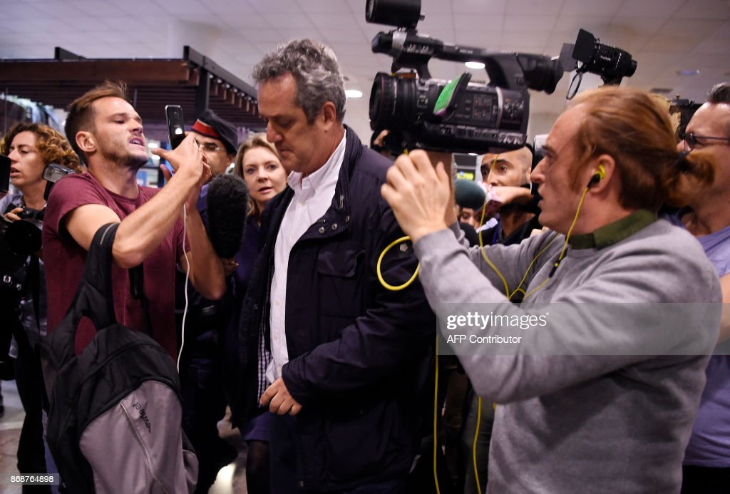 Catalan dismissed Interior chief Joaquim Forn (C) is followed by journalists upon his arrival at El Prat airport in Barcelona after flying from Brussel on October 31, 2017. Spain's top criminal court today summoned Catalonia's axed separatist leader for questioning, hours after he appeared in Brussels insisting he remained the 'legitimate president' of a region now under direct rule from Madrid. The National Audience in Madrid, which deals with major criminal cases, summoned Carles Puigdemont and 13 other former members of his administration, dismissed by Spain's central government last week, for November 2 and 3. PHOTO / Josep LAGO