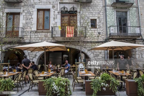 Catalan flag hangs from a balcony above a restaurant terrace on La Rambla de la Llibertat in Girona, Spain, on Tuesday, Aug 7, 2018. Girona FC is...