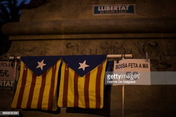 Catalan flags for sale while independence supporters gather at one gate of the closed Parliament's park as the Catalan Parliament is on session to...