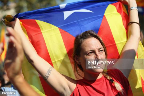 Catalan independence supporter holds the Catalan flag as she watches the Parliamentary proceedings televised outside the Parliament of Catalonia on...