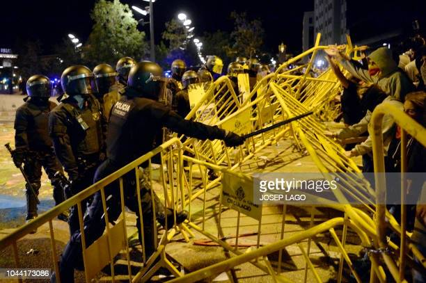A Catalan 'Mosso D'Esquadra' regional police officer uses the club as protesters try to break a security barrier outside the Spanish Govenment's...