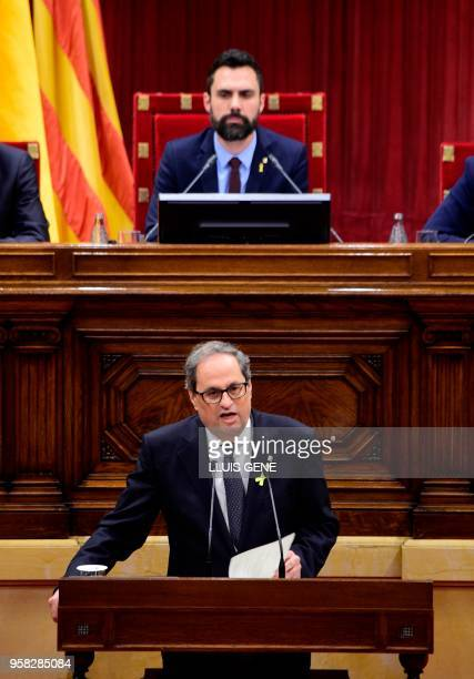 Catalan Parliament Speaker Roger Torrent listens to a speech by Junts per Catalonia MP and presidential candidate Quim Torra during a vote session to...