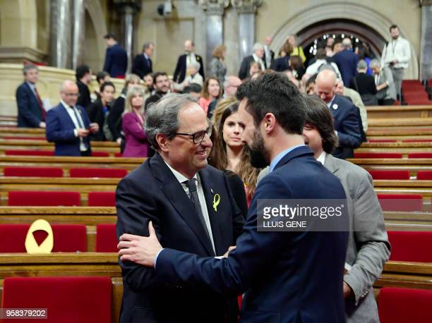Catalan Parliament Speaker Roger Torrent shakes hands with Junts per Catalonia MP and presidential candidate Quim Torra after being elected new...