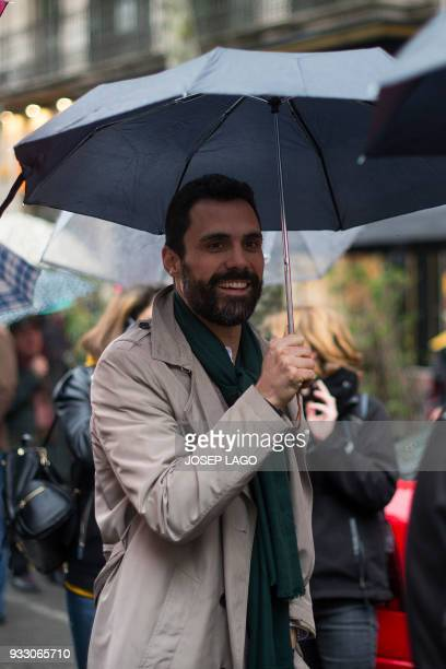 Catalan parliament speaker Roger Torrent walks with an umbrella on March 17 2018 in Barcelona during a demonstration titled 'The democratic and...
