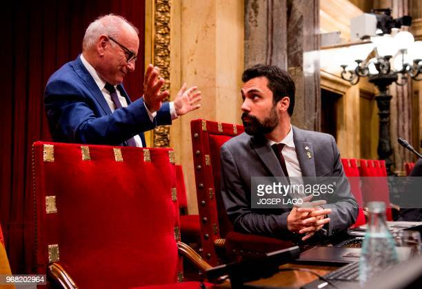 Catalan parliament's speaker Roger Torrent speaks with a parliament lawyer during a session of the Catalan regional parliament in Barcelona on June 6...