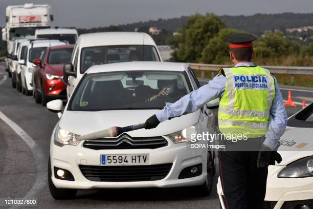 Catalan police officer controls traffic at a mobility checkpoint to ensure compliance with the rules of confinement On the 32nd day of confinement...