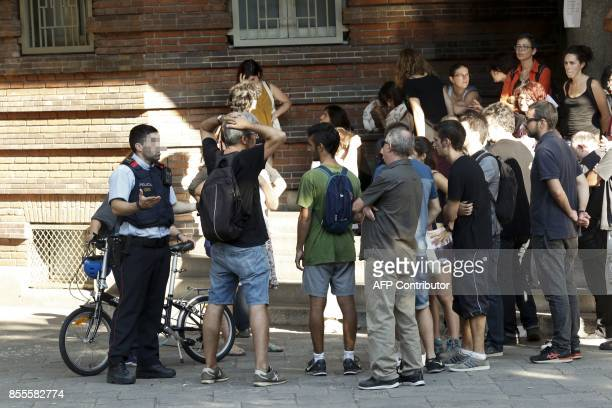 A Catalan police officer 'Mosso d'Esquadra' talks with proreferendum people inside the 'Escola Collaso i Gil' school on September 29 2017 in...