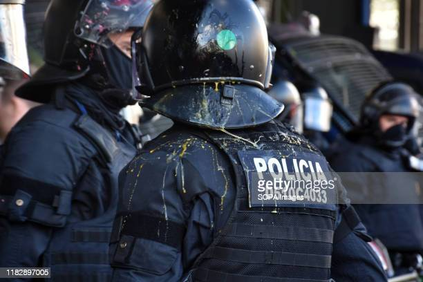Catalan police officer receives the impact of an egg thrown by protesters during the demonstration. The Catalan Police evict one by one without any...