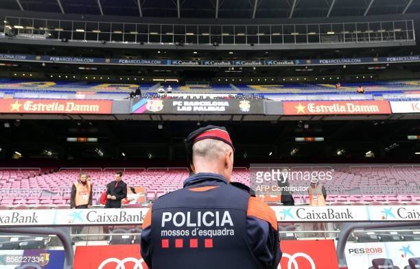 A Catalan police officer stands in front of empty stands after the decission of cancelling the Spanish league football match FC Barcelona vs UD Las...