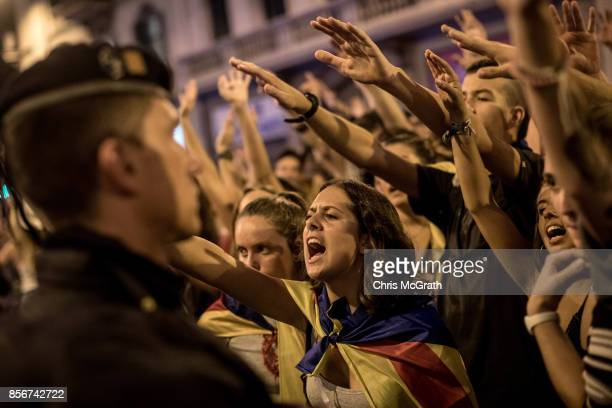 Catalan police officer stands in front of protesters as they shout slogans and gesture toward the General Direction of the National Police of Spain...