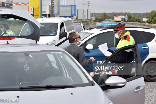 Catalan police officer wearing a surgical mask verifies the identification of a driver at a mobility checkpoint to ensure compliance with the rules...