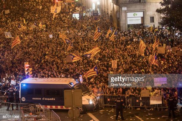 Catalan Police officers secure the area as thousands of people chant slogans outside the General Direction of the National Police of Spain building...