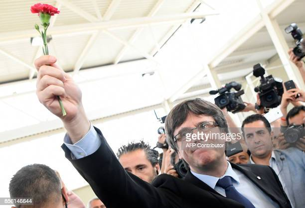 Catalan president Carles Puigdemont holds a carnation as he speaks with the media in Sant Julia de Ramis on October 01 in a referendum on...