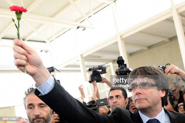 Catalan president Carles Puigdemont holds a carnation in Sant Julia de Ramis on October 01 during a referendum on independence for Catalonia banned...