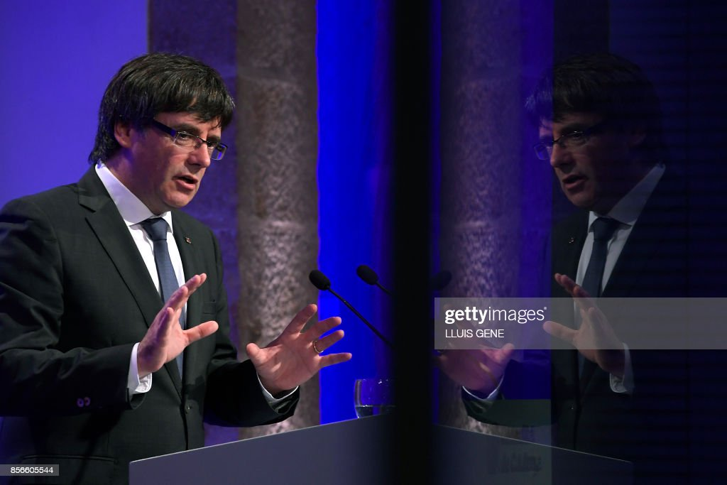 TOPSHOT - Catalan president Carles Puigdemont is reflected on a window during a press conference in Barcelona, on October 2, 2017. Catalonia's leader Carles Puigdemont said the region had won the right to break away from Spain after 90 percent of voters taking part in a banned referendum voted for independence, defying a sometimes violent police crackdown and fierce opposition from Madrid. /