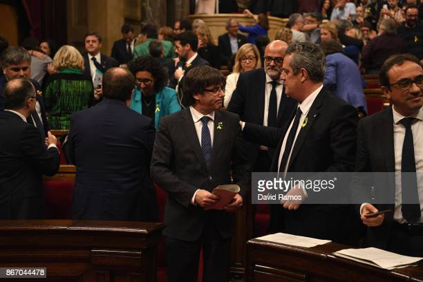 Catalan President Carles Puigdemont is seen with other members of Parliament as they react to the news that the Catalan Parliament has voted in...