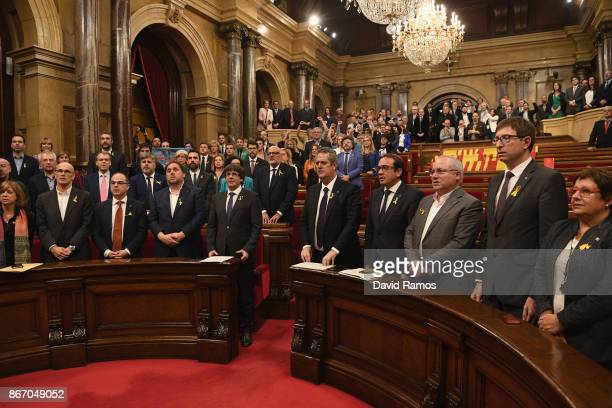 Catalan President Carles Puigdemont is seen with other members of Parliament as they sing the national anthem after the news that the Catalan...
