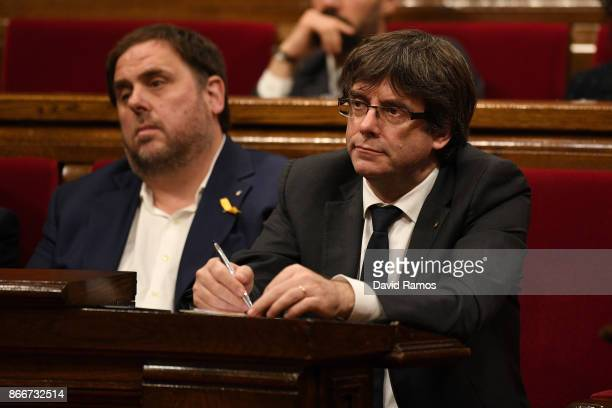 Catalan President Carles Puigdemont sits with Catalan vicepresident Oriol Junqueras during a meeting of the Catalan government at the Catalan...