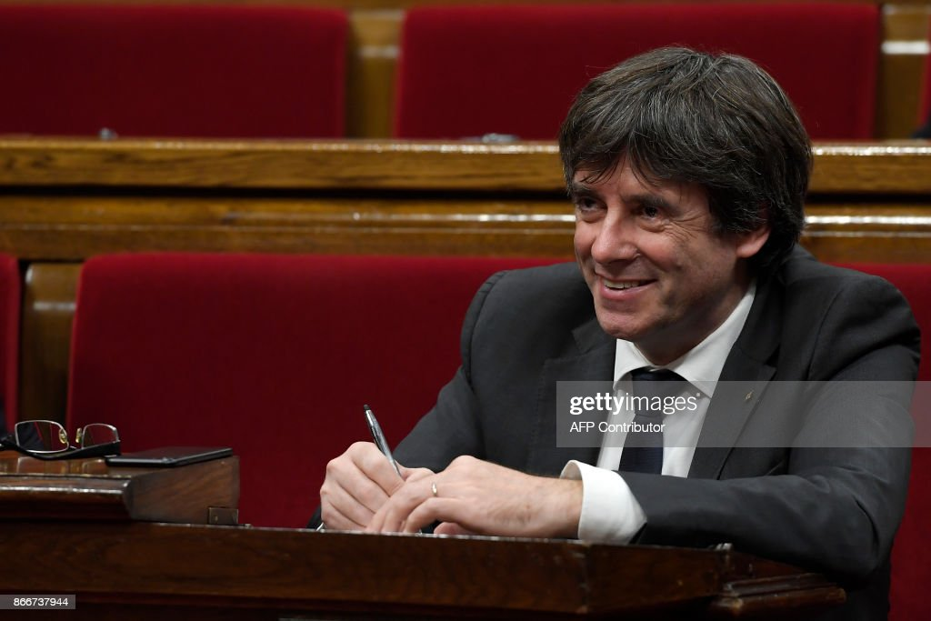 Catalan president Carles Puigdemont smiles during a session of the Catalan parliament in Barcelona on October 26, 2017. Catalan leader Carles Puigdemont said today he had considered calling elections to prevent Madrid from seizing control of the region, but decided there were no 'guarantees' to do so. He went on to say that it was now 'up to the (regional) parliament to decide on how to respond to the central government's planned takeover of Catalan political powers following an outlawed independence referendum. GENE