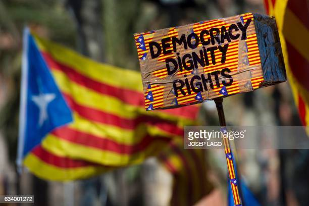 A Catalan proindependence 'estelada' flag flies in background of a cardboard box with the 3 words Democracy Dignity and Rights outside the TSJC in...