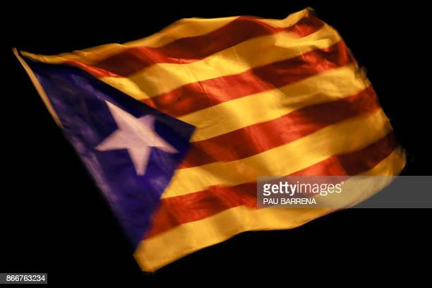A Catalan proindependence 'Estelada' flag waves near the Catalan Parliament in Barcelona on October 26 2017 Catalan opposition lawmakers pleaded with...