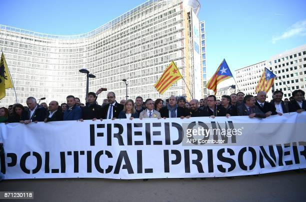 Catalan proindependence mayors hold a banner as they demonstrate to show solidarity with detained officials in Spain on November 7 2017 in front of...