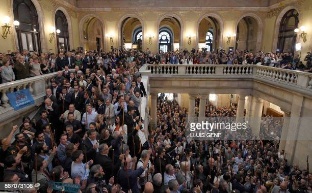 Catalan proindependence mayors raise their batons as they gather in the parliament after a session of the Catalan parliament in Barcelona on October...
