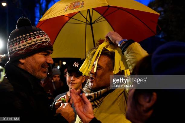 A Catalan proindependence protester talks with an antiindependence protester holding an umbrela bearing he colors of the Spanish flag on February 25...