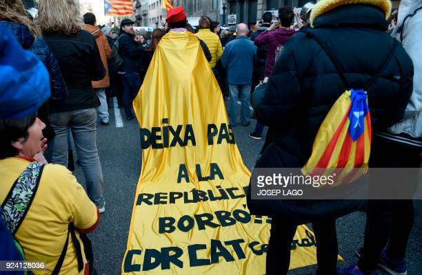Catalan proindependence protester wears a cape reading Borbon leave room for the Republic during a demonstration against the visit of Spain´s King...