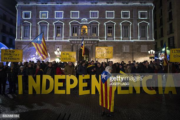 Catalan proindependence supporters hold Catalan proindependence flags and letters reading 'Independence' during a demonstration in Saint Jaume square...