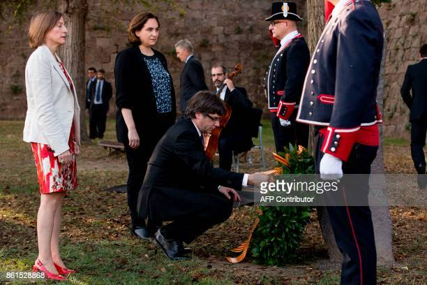 Catalan regional government president Carles Puigdemont lays a wreath next to Catalan parliament president Carme Forcadell and Barcelona mayor Ada...